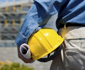 commercial construction worker looking at a project holding a hard hat